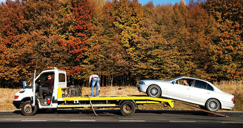 A tow truck loading a car